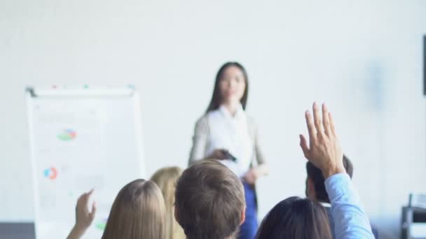 Group Of Business People Asking Question To Businesswoman Leading Presentation Discussing Financial Report
