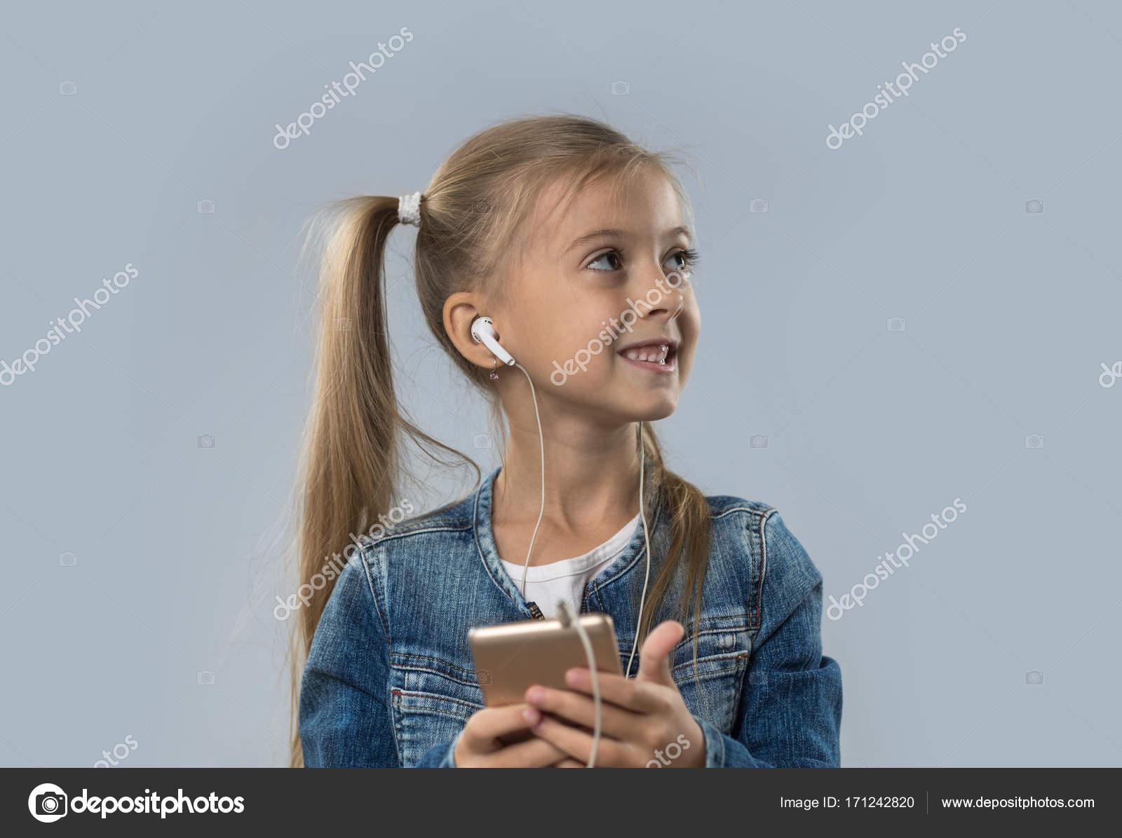 Beautiful Little Girl Using Smart Phone Listen Music Wear Earphones