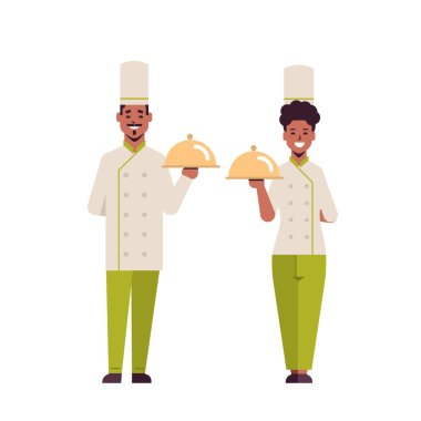 cooks couple professional chefs holding covered platters serving trays african american woman man restaurant workers in uniform standing together cooking food concept flat full length