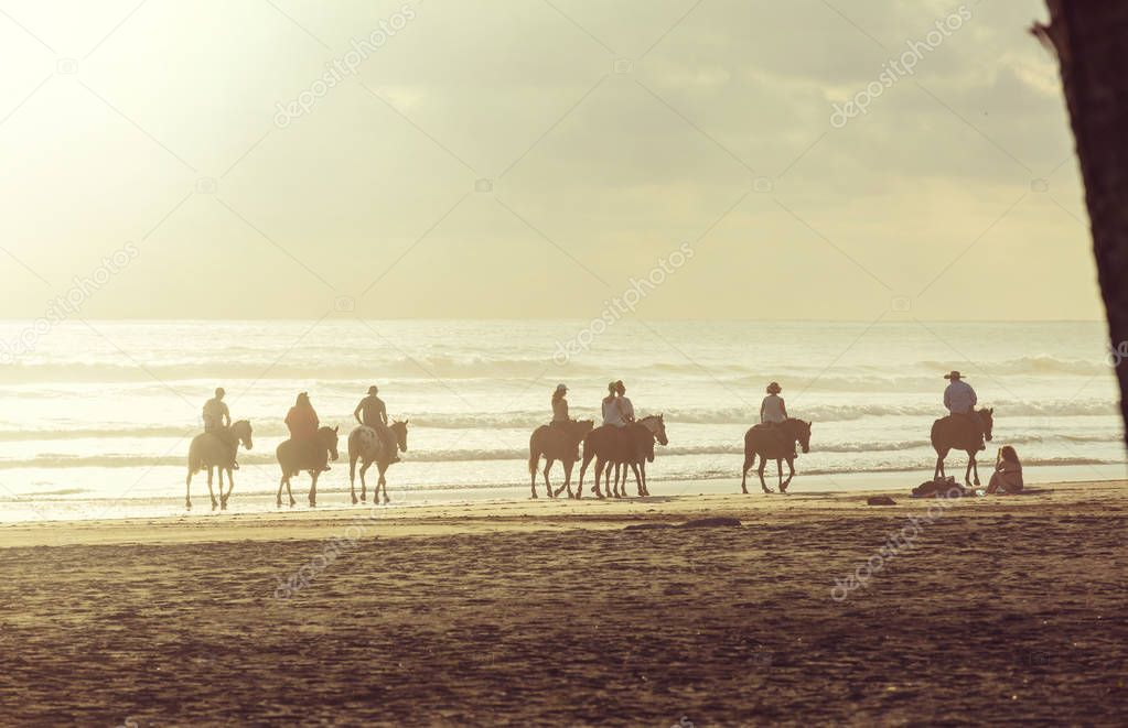 People horseback riding on shore in Costa Rica, Central America