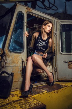 GIRL TRACTOR DRIVER WITH A PIPE WRENCH