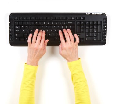 Hands in yellow jacket and black keyboard
