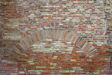 Old red brick wall with arch vintage texture background