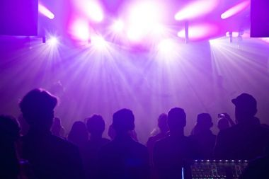 Rock band silhouettes on stage at concert.