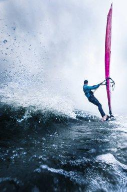 Windsurfer surfing towards horizon