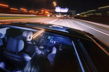 couple of friends in a luxury car driving at night