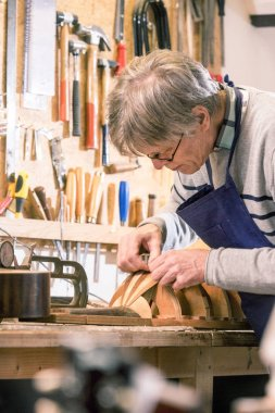 Luthier carefully carving the shape of a lute
