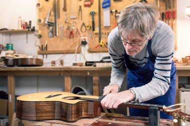 Luthier filing the frets of an acoustic guitar