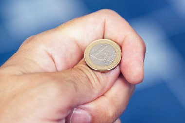 Businessman hand tossing coin to flip on heads or tails