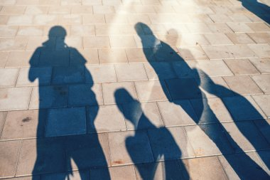 People casting shadows on the pavement