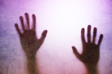 Trapped person, back lit silhouette of hands behind matte glass