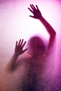 Trapped woman, back lit silhouette of hands behind matte glass