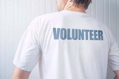 Guy wearing shirt with Volunteer label printed on back