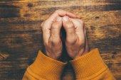 Draufsicht der religiösen männlichen gekreuzten Händen im Gebet