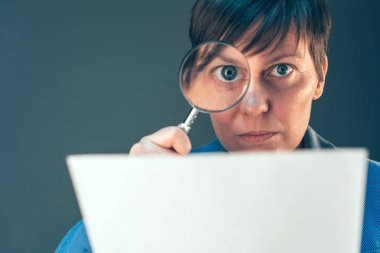 Female tax inspector looking at document with magnifying glass