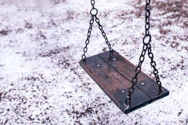 Empty swing on children playground under snow