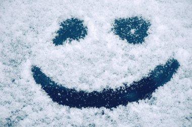 Happy smiley emoticon face in snow