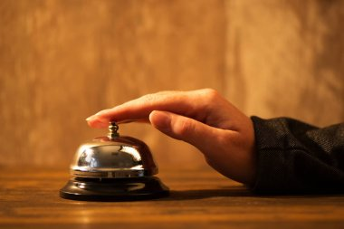 Businesswoman ringing hotel reception bell, warm retro toned image with selective focus stock vector