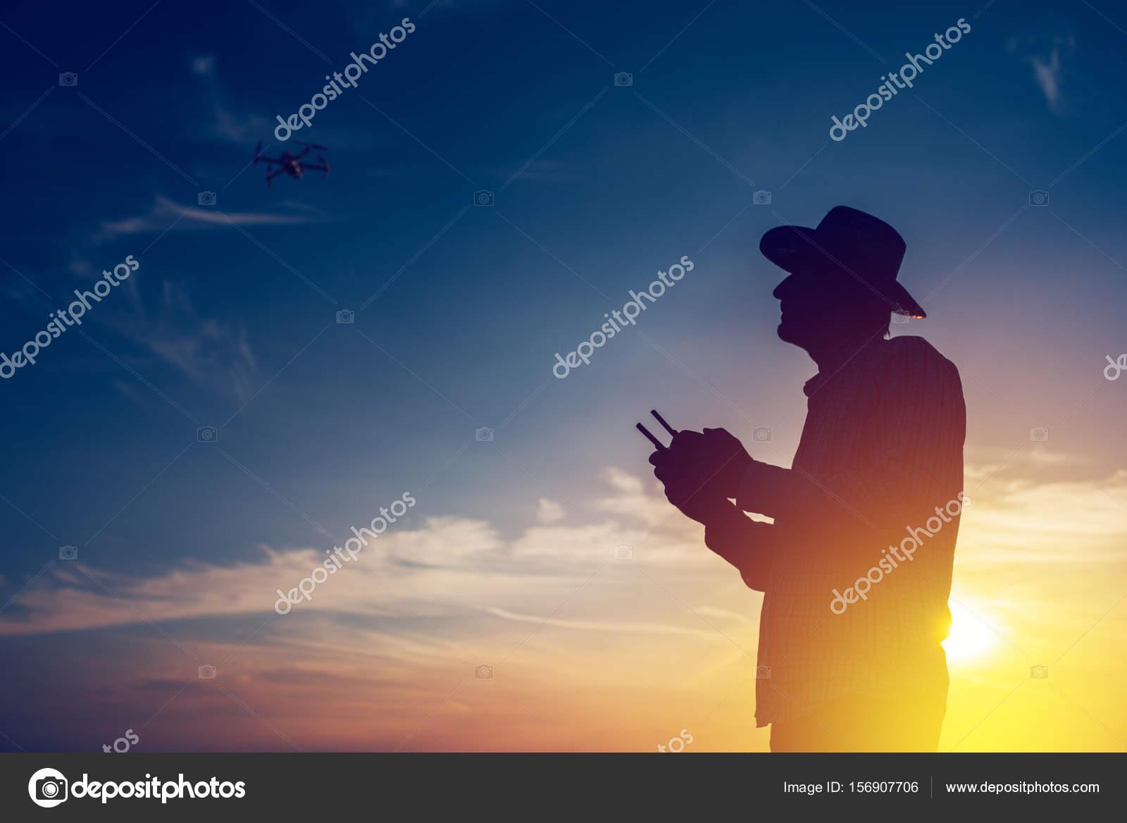 Silhouette of farmer using drone remote control — Stock