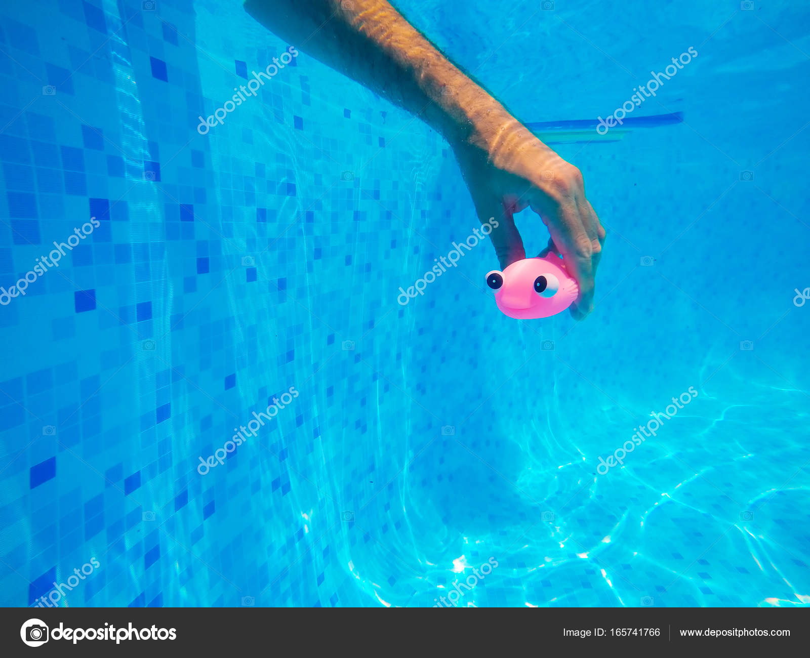 Man playing with generic rubber fish toy in swimming pool — Stock ...