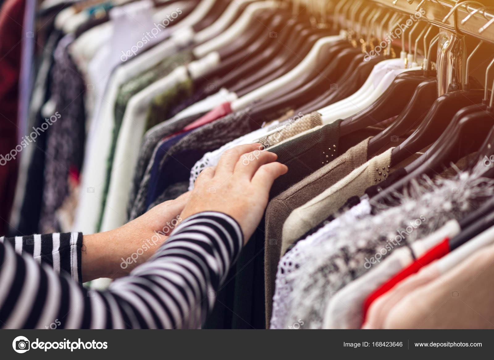 07384c0a905d Γυναίκα περιήγηση μέσα από ρούχα από δεύτερο χέρι λαϊκή αγορά– εικόνα  αρχείου