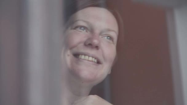 Happy woman smiling behind the window
