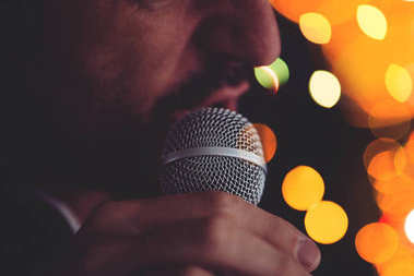 Man sings karaoke in a bar at night with festive bokeh light effect, selective focus stock vector