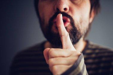 Man saying hush or be quiet