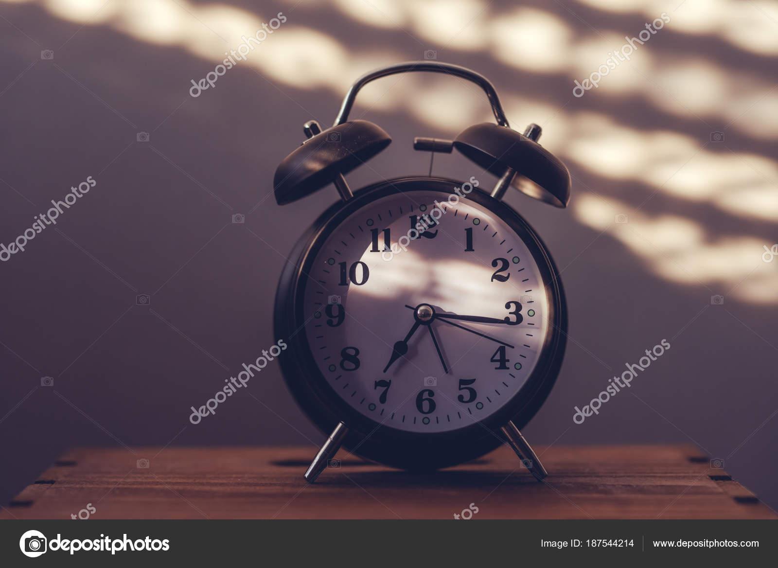 Wecker Auf Dem Nachttisch Im Schlafzimmer Tickende Zeit Im Frühen Morgen  Mit Sonnenlicht Und Schatten An Der Wand Im Hintergrund U2014 Foto Von  Stevanovicigor