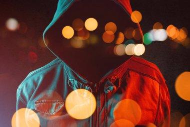 Faceless hooligan with hoodie in urban surrounding