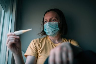Woman in self-isolation measuring body temperature electronic digital thermometer. Female person with face protective respiratory mask, selective focus.