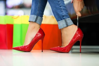 woman fitting red elegant stilettos