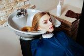 Mladá žena mytí vlasů v salonu