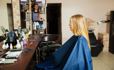 Young woman waiting for hairdresser in salon