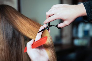 Hairdresser making hairstyle with scissors