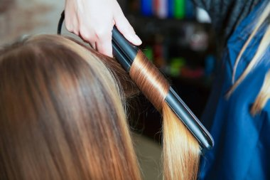 hairdresser making hairstyle with curling iron