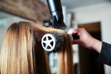 Making hairstyle using hair dryer