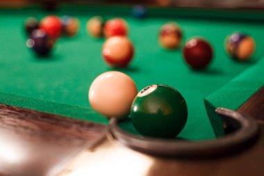 billiard balls near pocket of billiard table