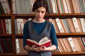 Fotografia giovane donna in biblioteca universitaria