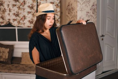 Surprised woman with half-open suitcase