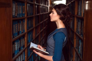 Young woman with notebook in library