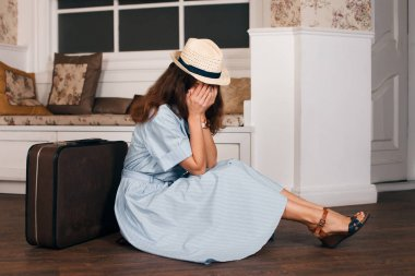 woman sitting on floor with suitcase
