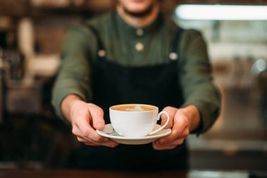 Barista holds cup of coffee