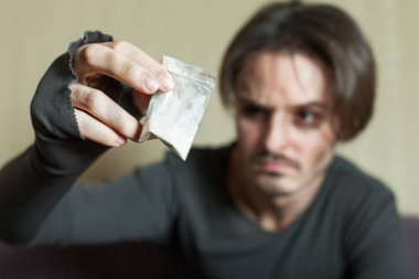 Man with cocaine dose in hand