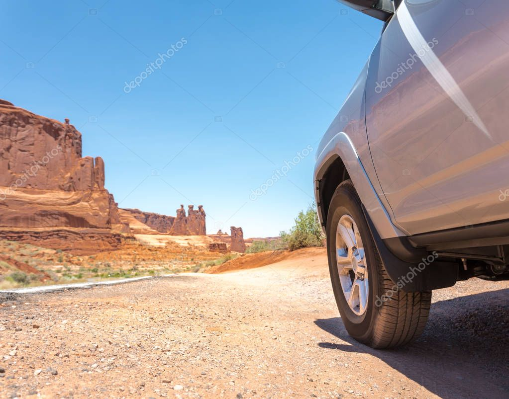 car on road along red rocks