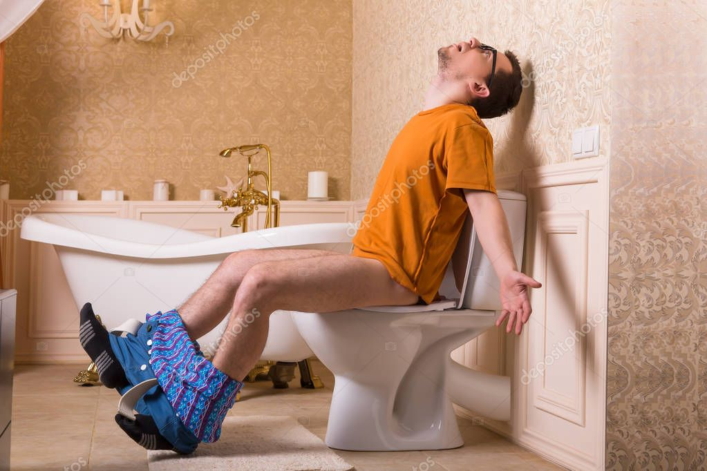 Young woman sitting on toilet bowl against white
