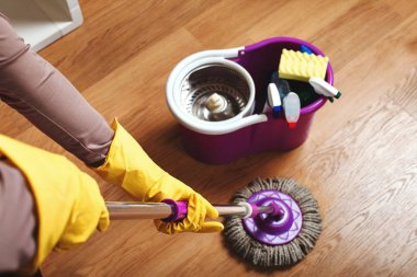 hands in gloves washing floor with mop