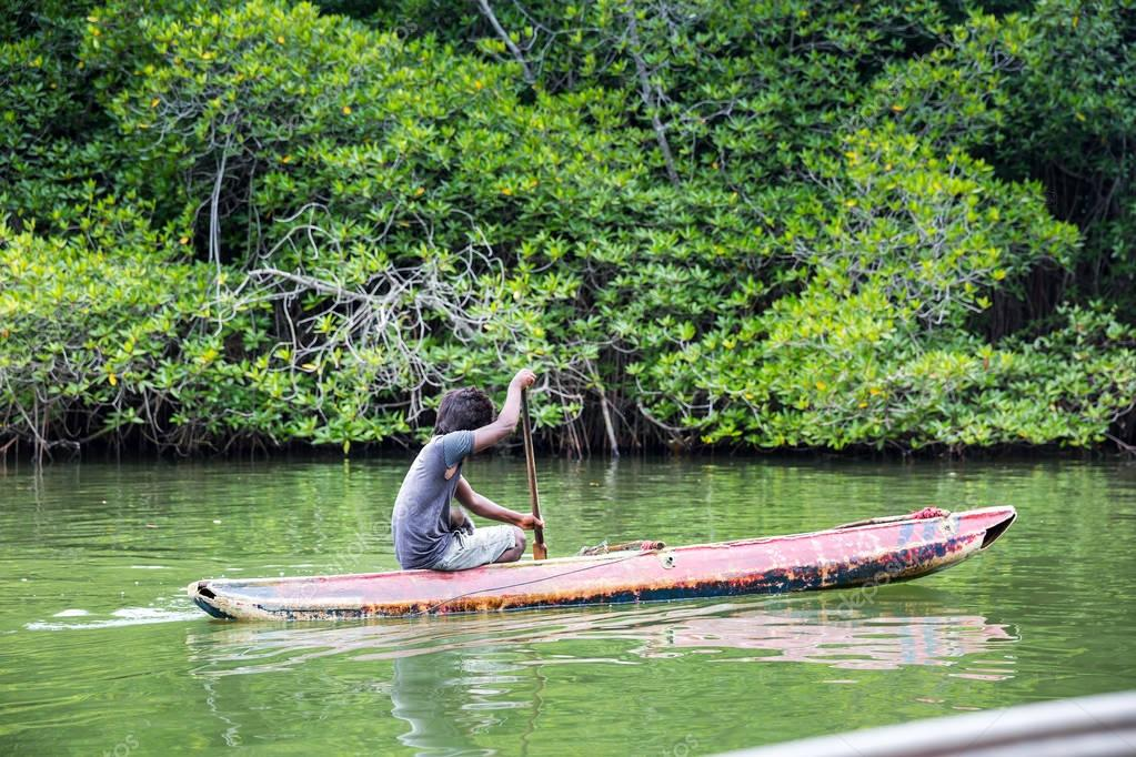 man in boat floating on river