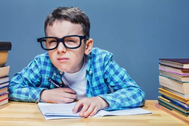 Schoolboy at desk with many books
