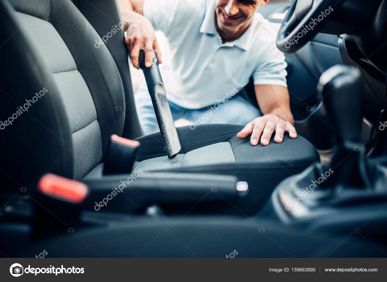 de man reinigen van auto interieur met stofzuiger op carwash station auto reiniging foto van nomadsoul1